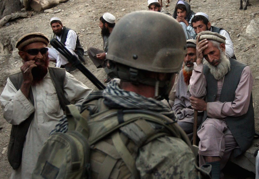 Village elders spoke with a U.S. Marine as Afghan forces search for weapons October 25, 2008 in the Korengal Valley of Kunar Province in eastern Afghanistan. Taliban insurgents enjoyed widespread public support in the contested valley, site of some of the heaviest fighting between U.S. forces and Taliban insurgents.