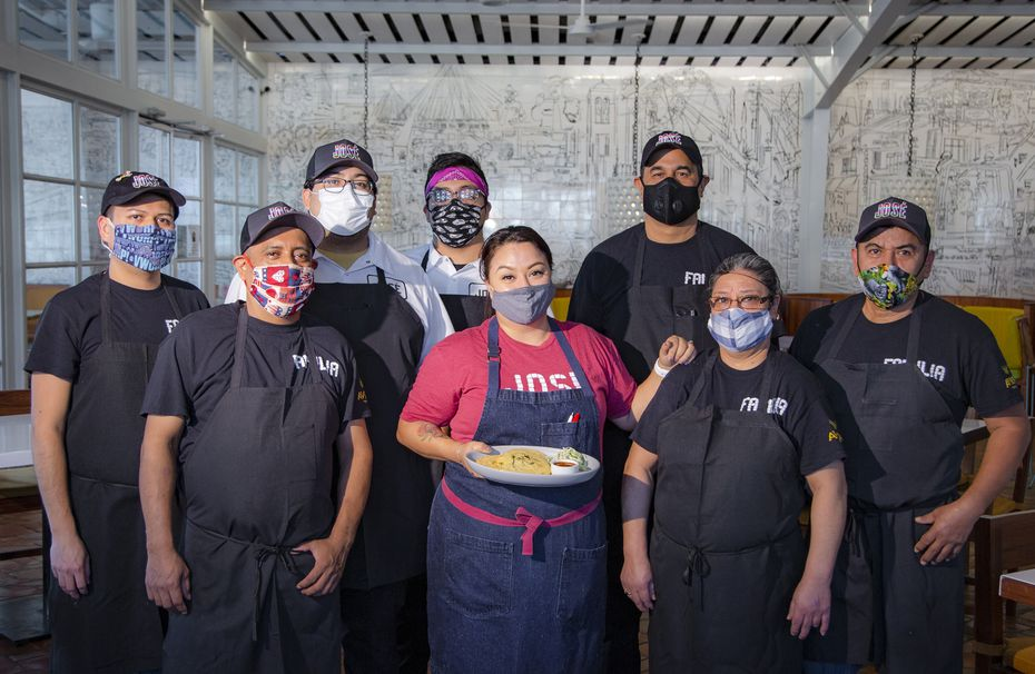 Anastacia Quiñones-Pittman, head chef of the Dallas restaurant José, poses with her staff with a plate of pupusas.