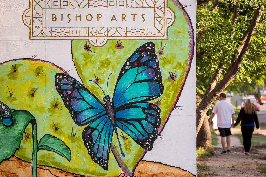 Pedestrians walk past a temporary installation of paintings of flora and fauna at Bishop and Melba streets in the Bishop Arts District.