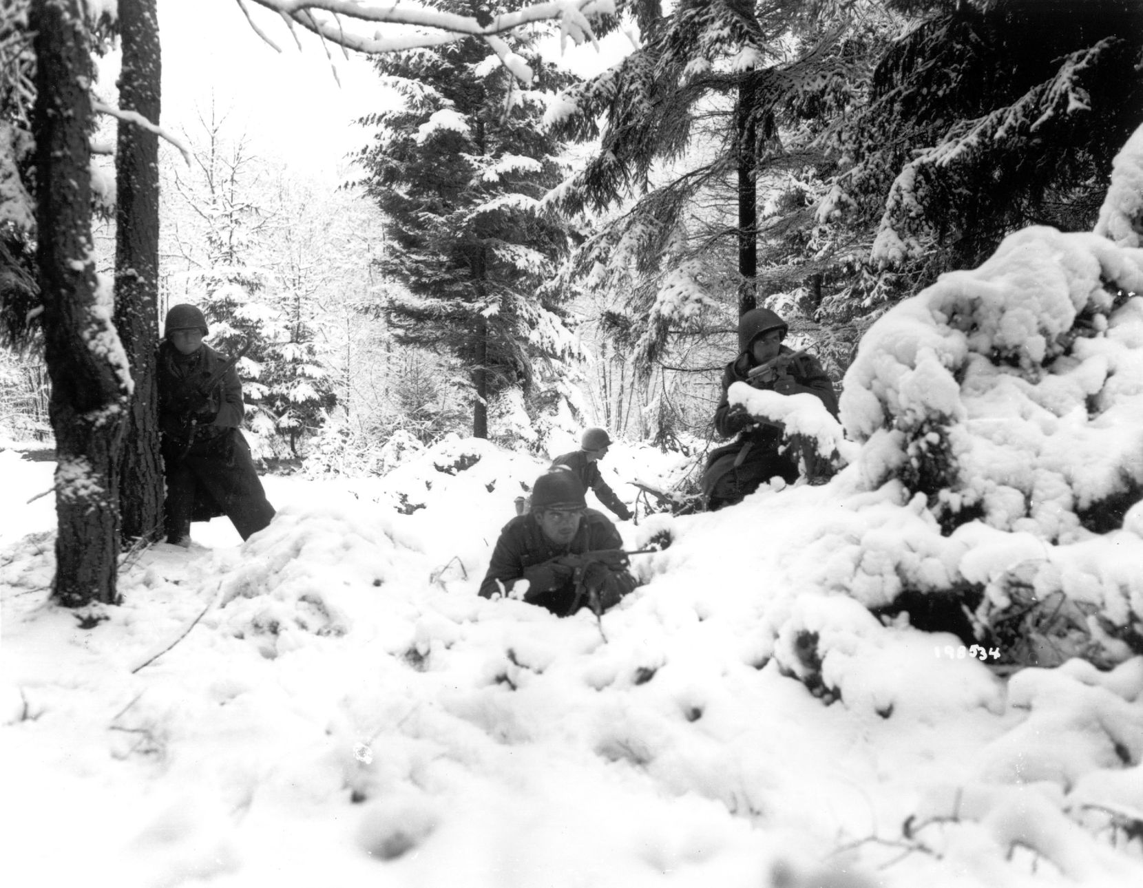 American infantrymen of the 290th Regiment move through fresh snowfall as they advance against German troops in a forest near Amonines, Belgium, on January 4, 1945.