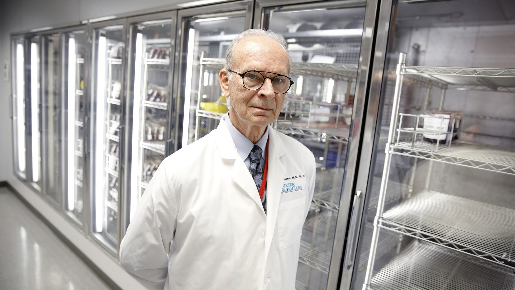 """President and CEO of Carter BloodCare, Dr. Merlyn Sayers, is pictured before an empty cooler at their headquarters in Bedford, Texas, Wednesday March 18, 2020. The Center is putting out the word that they have a shortage of blood. """"Something like 600 people a day in our community need a transfusion. They can't wait 'til coronavirus has blown over."""", he said. (Tom Fox/The Dallas Morning News)"""