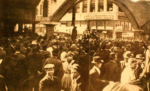 Close-up view of a postcard that depicts a public lynching in Dallas. In this photo, taken on March 3, 1910, a vast mob of 10,000, many of them children, stand shoulder to shoulder around Allen Brooks, a black man. He is lynched from a telephone pole at Elm and Akard streets in downtown Dallas.