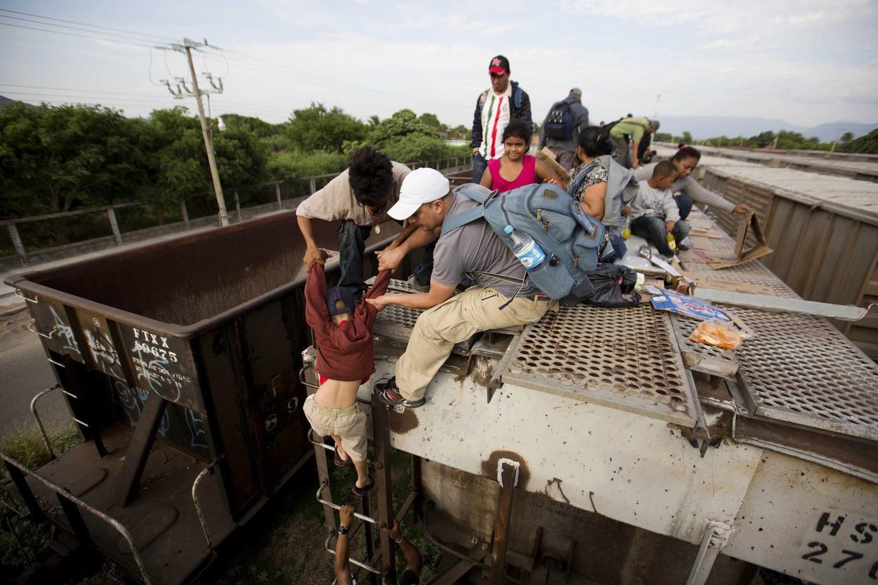 Un niño recibe ayuda para bajarse de un tren de carga en Ixtepec, Puebla. (AP/EDUARDO VERDUGO)
