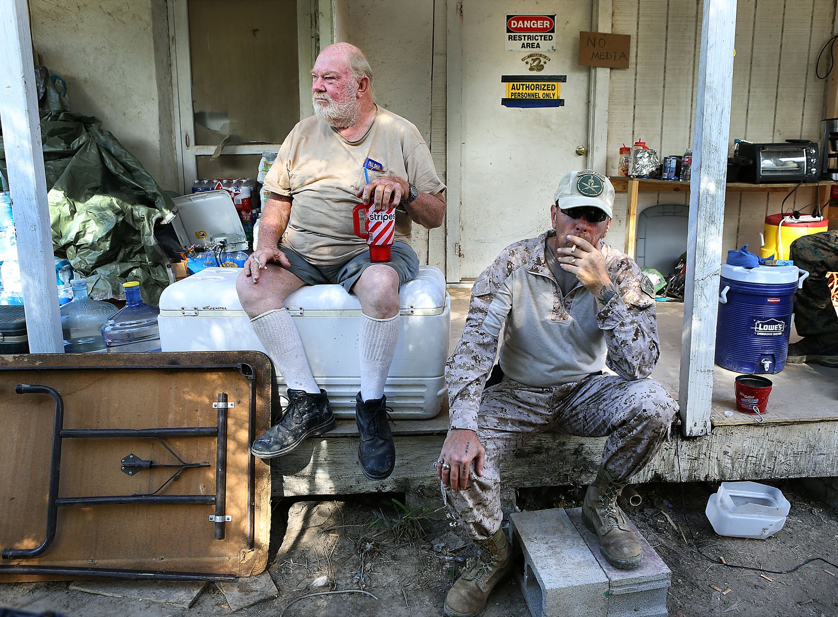 Kevin Massey, right, takes a drag on a cigarette as he sits with land owner Rusty Monsees Jr. Monsees asked the militia group called Camp Lone Star, to set up camp on his property along the Rio Grande River in Brownsville on September 10, 2014