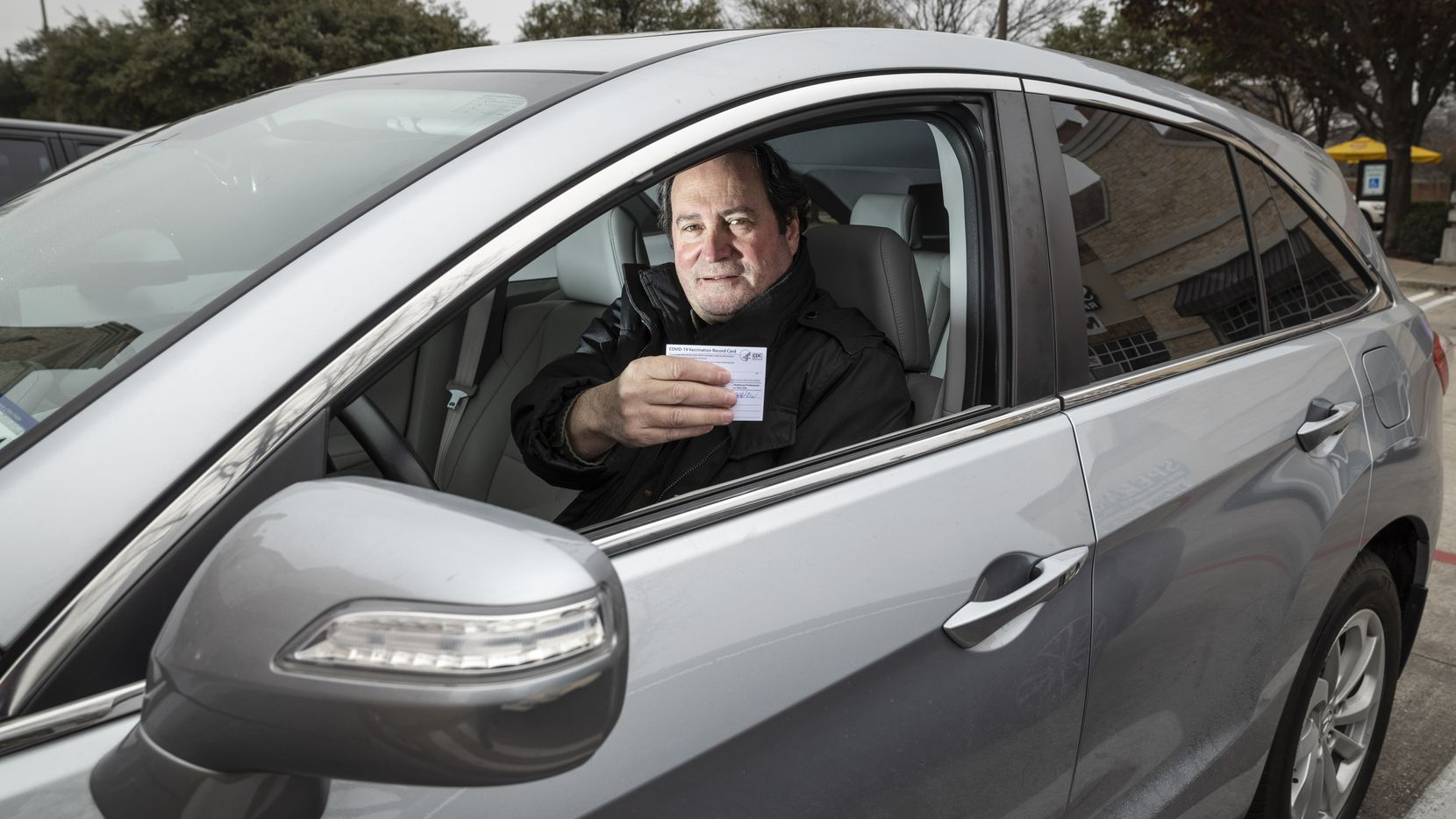 Alan Samuels, 59, of Dallas holds the COVID-19 vaccination card he received after getting his first shot by traveling to Austin from Dallas and waiting an hour to receive it.