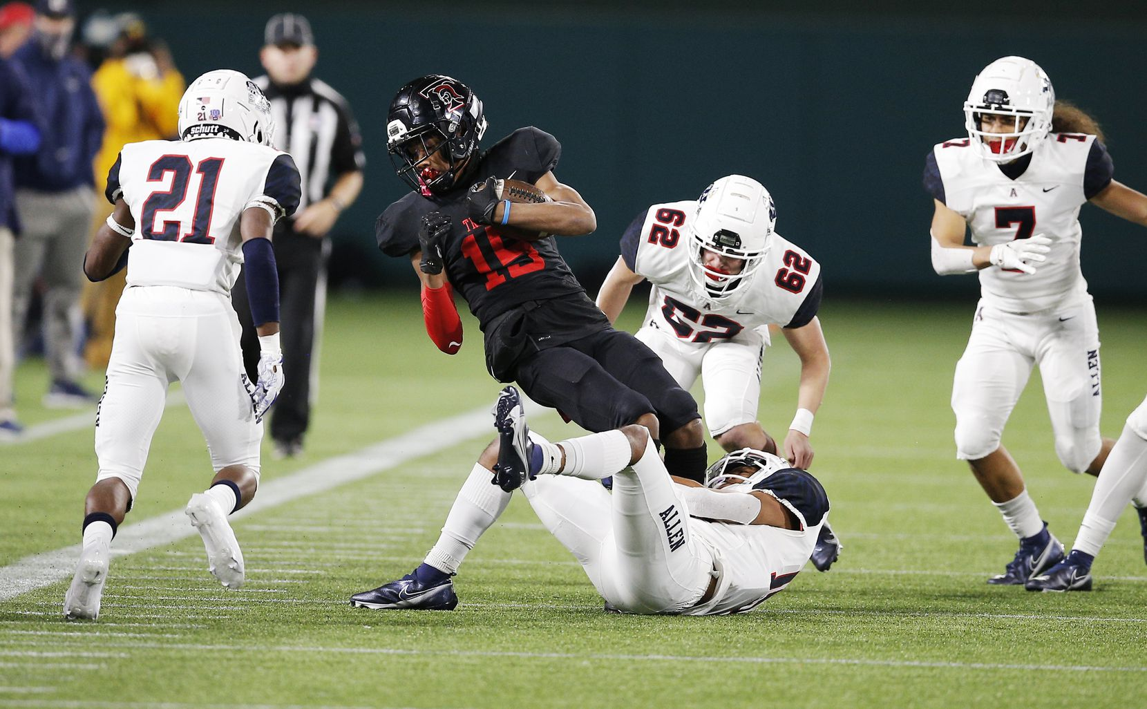 Euless Trinity junior wide receiver Pofele Ashlock (15) is tackled by Allen senior defensive back Alexander Green during the first half of a high school Class 6A Division I Region I semifinal football game at Globe Life Park in Arlington, Saturday, December 26, 2020. (Brandon Wade/Special Contributor)