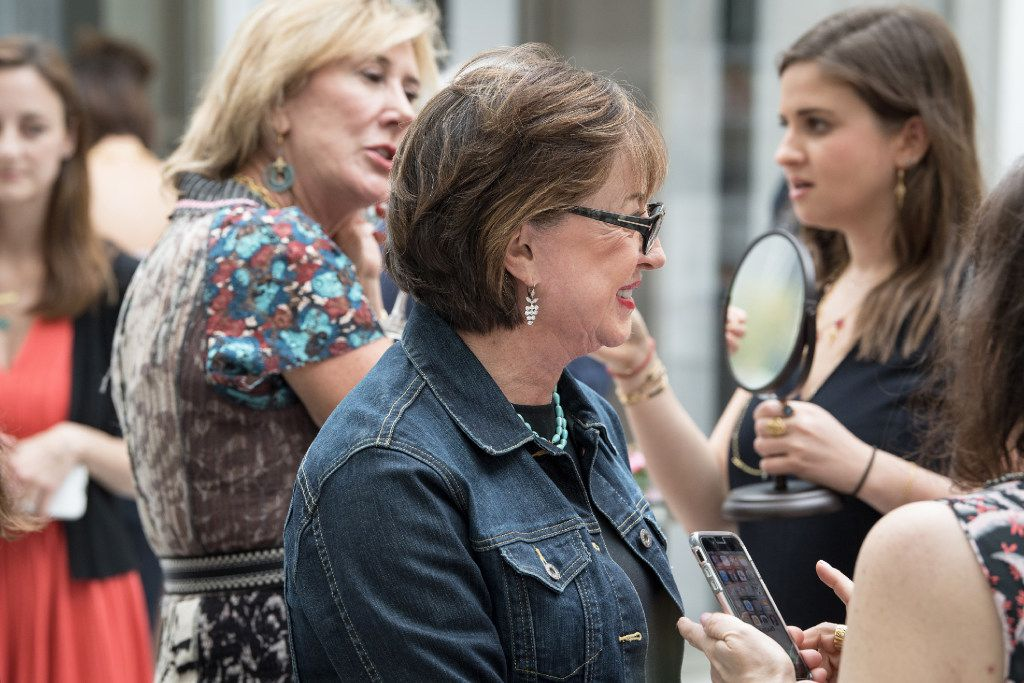 Alysa Teichman, background right, holds a mirror for collector Karen Carney, while she tries on Cathy Waterman earrings. Priscilla Beshears, foreground, is wearing Waterman earrings she purchased years ago.