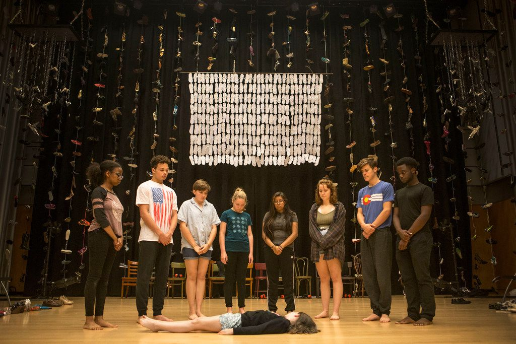 People surround Maren Bennett, 10, during a rehearsal of Cry Havoc Theater's Babel at the Winspear Opera House in Dallas on June 30.