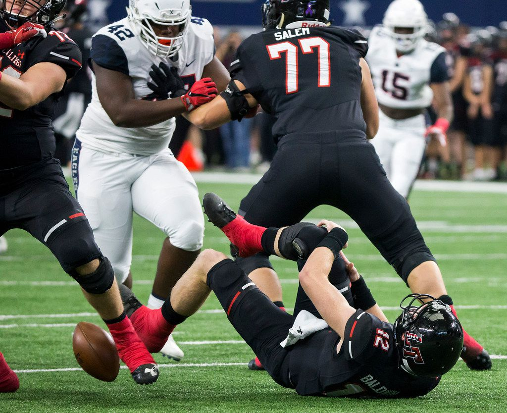 Lake Travis quarterback Matthew Baldwin (12) fumbles as he collapses to the turf grabbing his injured right knee as Allen defensive lineman Jayden Jernigan (42) fights past Lake Travis offensive lineman Andrew Salem (77) to recover the fumble and take it in for a touchdown during the first half of the Class 6A Division I state championship game at AT&T Stadium on Saturday, Dec. 23, 2017, in Arlington, Texas. (Smiley N. Pool/The Dallas Morning News)