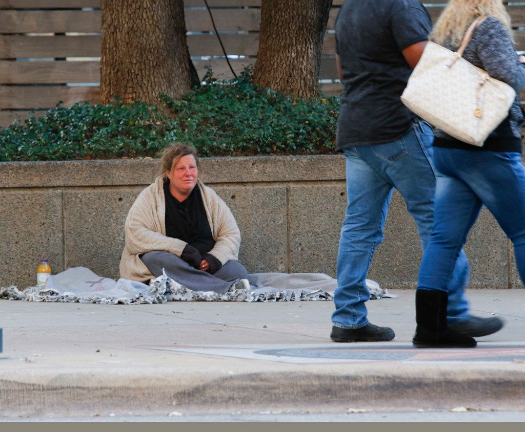 Lisa Kelso watches pedestrians pass her on St. Paul St. at the intersection of Jackson St. in downtown Dallas Monday, December 11, 2017.  She said she has been on the street for about a year. (Ron Baselice/The Dallas Morning News)