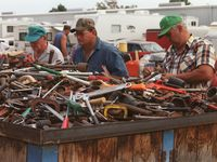 Men rummage through a huge container of used tools at a Canton First Monday Trade Days.