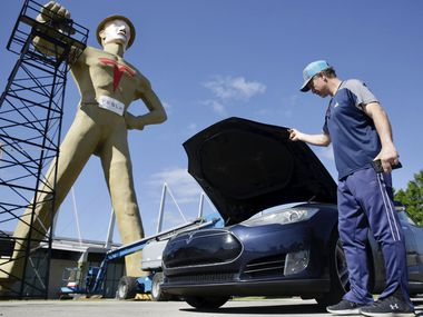 Andrew Nelson lifts the hood of his Tesla Model S in front of the Golden Driller as it gets a Tesla facelift Tuesday, May 19, 2020.