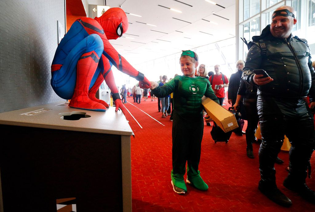 Lucas Hightower (Green Lantern), 8, of Bryan-College Station, Texas (center) receives a fist bump from Patrick Belcher (Spiderman) of Richardson.