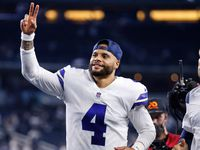 Dallas Cowboys quarterback Dak Prescott (4) runs off the field waving to those in the crowd following their win over the Eagles at AT&T Stadium in Arlington, Monday, September 27, 2021.