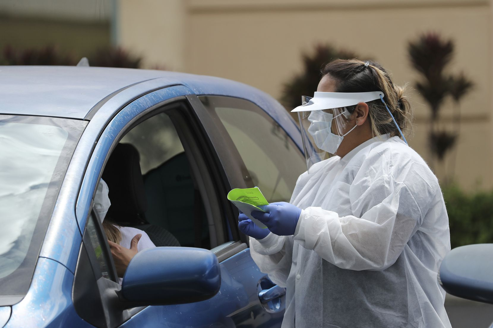 A medical worker at a facility in Pearl City, Hawaii, was fully equipped with eye and body protection to test patients in their vehicles.