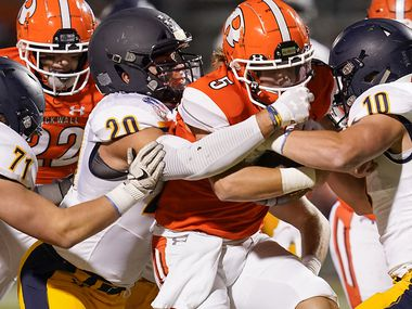 Rockwall quarterback Lake Bennett (5) is brought down by Highland Park's Patrick Turner (20) and Marshall Landwehr (10) during the first half of a high school football game on Friday, Oct. 16, 2020, in Rockwall, Texas.