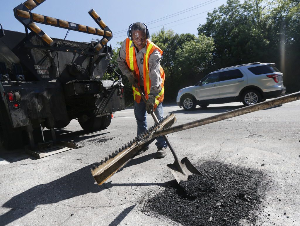 City of Dallas Street Services employee Rodney Chism helps fix a pothole on Harry Hines Boulevard.