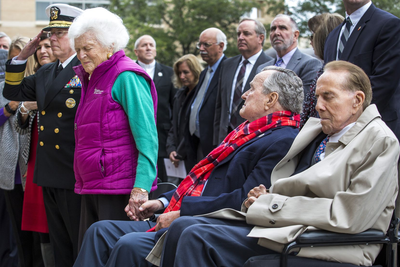 """2016: Barbara Bush stands beside former President George H.W. Bush (seated) and former Sen. Bob Dole during the playing of """"Taps"""" during a commemoration of the 75th anniversary of Pearl Harbor at the George Bush Presidential Library in College Station, Texas."""