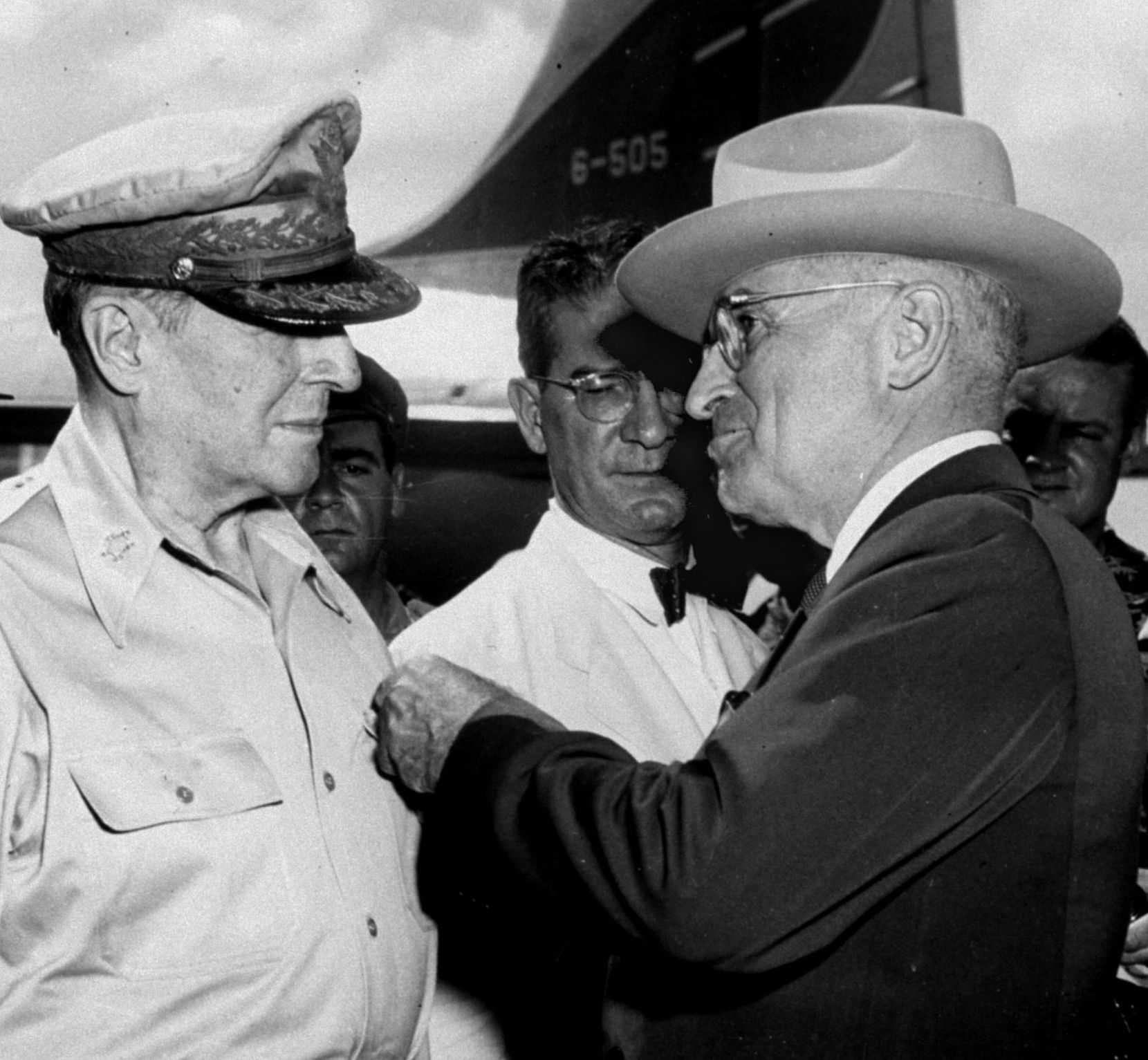 President Truman pins the Distinguished Service Medal on the shirt of Gen. Douglas MacArthur during a ceremony at the airstrip on Wake Island, on Oct. 14, 1950 while John J. Muccio, United States ambassador to Korea, watches.