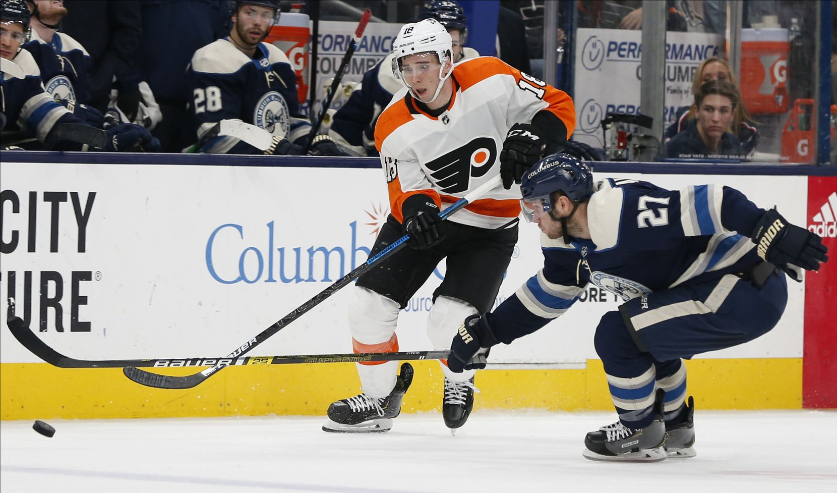 Philadelphia Flyers' Tyler Pitlick, left, dumps the puck past Columbus Blue Jackets' Ryan Murray during the third period of an NHL hockey game Wednesday, Nov. 27, 2019, in Columbus, Ohio. The Flyers won 3-2. (AP Photo/Jay LaPrete)