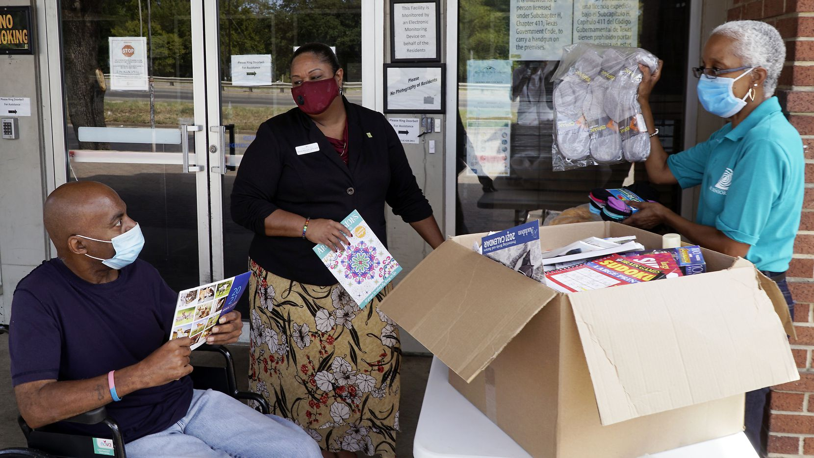 Friendly Visitor Coordinator Marsha Evans (right) delivers donations to Modern Senior Living resident Willie Wilson (wheelchair) and Administrator Monté Mitchell in Dallas, Texas on Friday, August 14, 2020.  (Lawrence Jenkins/Special Contributor)