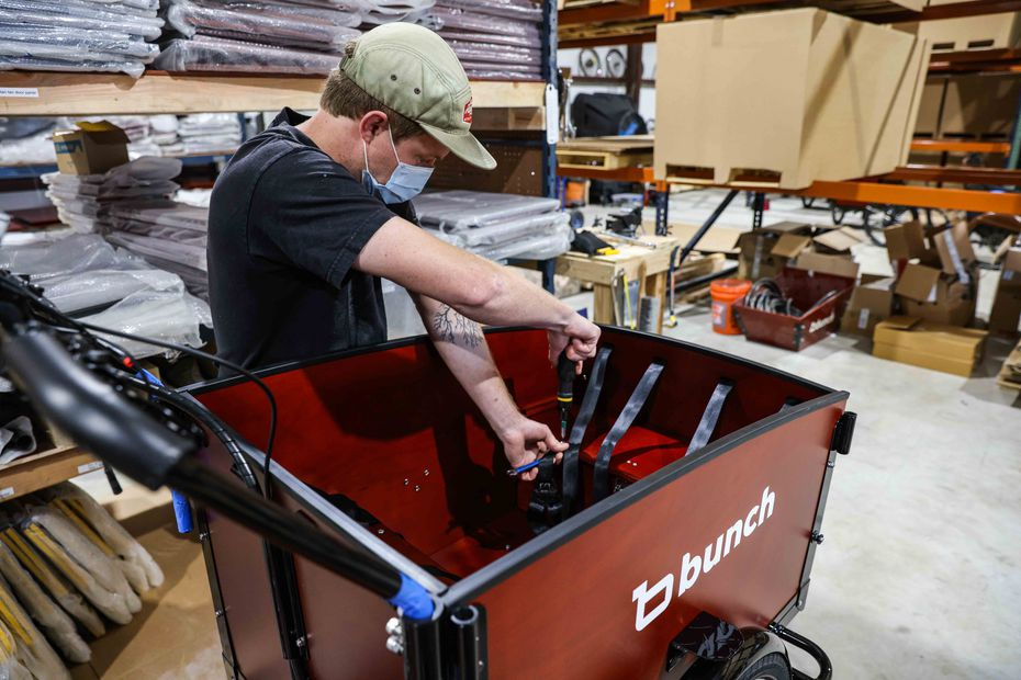 Logan Holland assembles a bike at Bunch Bikes in Denton on Wednesday, March 24, 2021. (Lola Gomez/The Dallas Morning News)