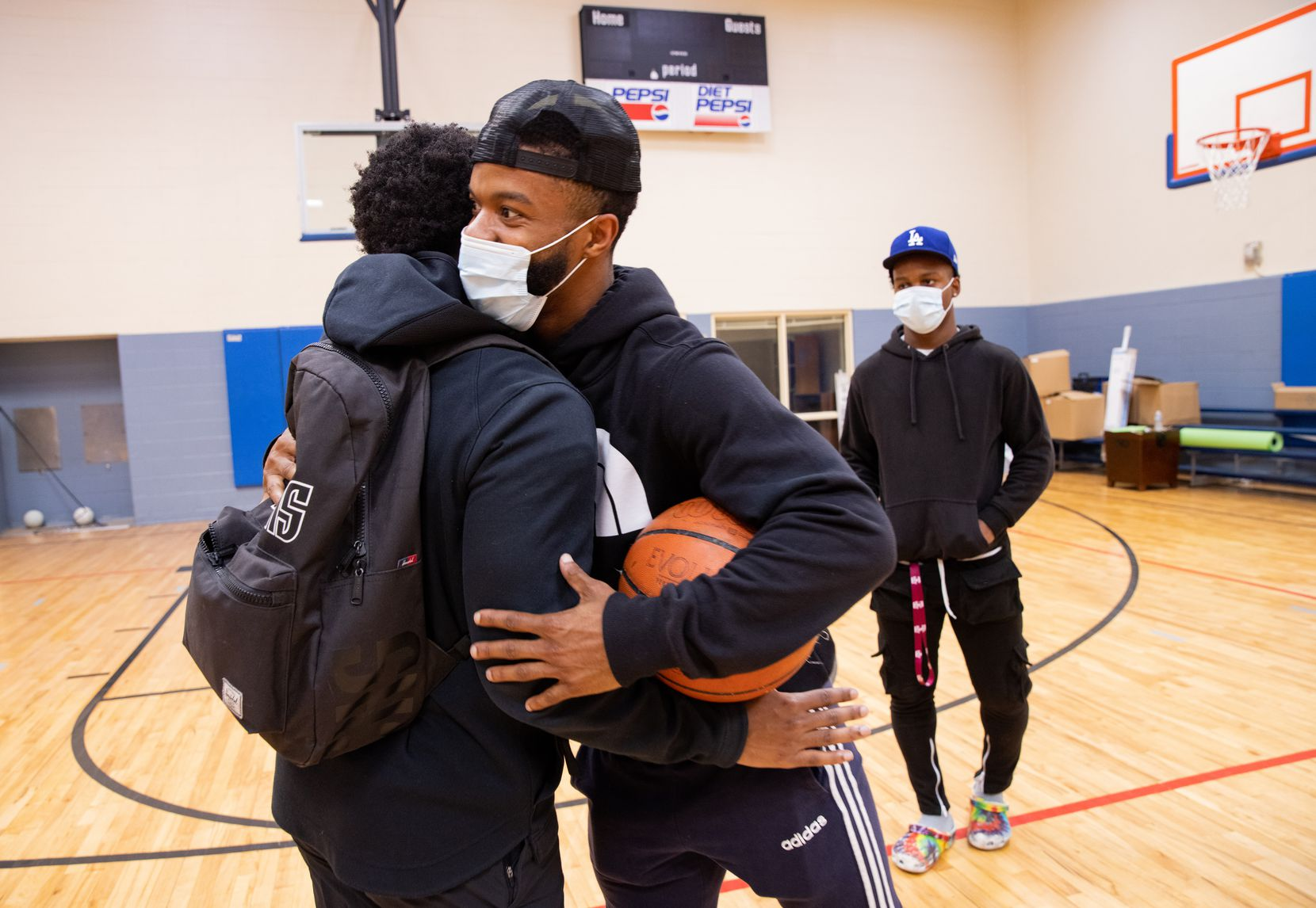 Xavier Henderson, left, For Oak Cliff's director of strategy, greets Frank Byers Jr. in the Moorland gym Friday. Byers, a  Gates Millennium Scholar who attends Texas A&M, said he wholeheartedly believes in what For Oak Cliff is trying to do for his community.