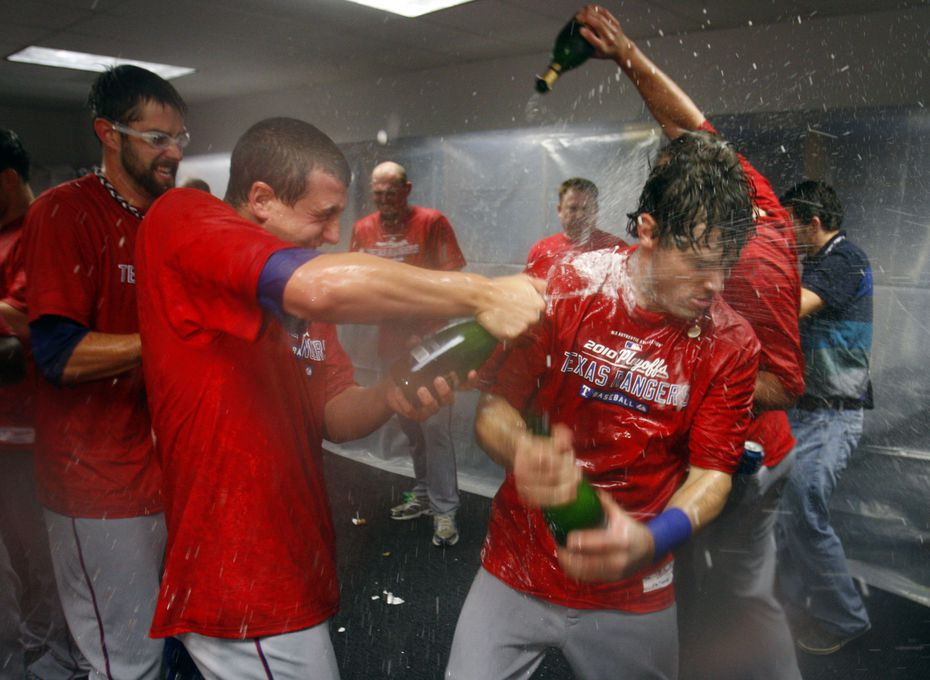FILE - Derek Holland (left) sprays Ian Kinsler (center) with champagne as the Rangers celebrate their win over the Rays in Game 5 of the ALDS at Tropicana Field in St. Petersburg, Fla., on Oct. 12, 2010.