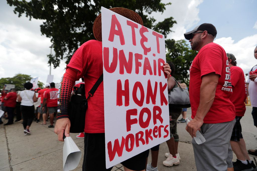 Members of the Communications Workers of America walk a picket line outside of an AT&T office, Monday, Aug. 26, 2019, in Miami. CWA union members in the southeast went on strike several weeks ago over unfair labor practices by management during negotiations for a new contract. Now, they're speaking out about an emerging activist investor.