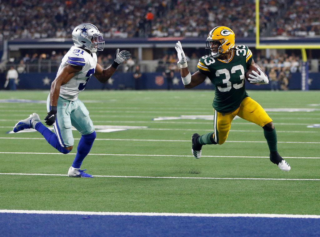 Green Bay Packers running back Aaron Jones (33) waves towards Dallas Cowboys cornerback Byron Jones (31) as he makes his way to the end zone for a touchdown during the second half of play at AT&T Stadium in Arlington, Texas on Sunday, October 6, 2019. The Green Bay Packers defeated the Dallas Cowboys 34-24.