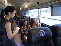 Sarah Moore, left, attendant for Vonlane, explains what guests can order before their bus departed Dallas en route to Austin in 2015.