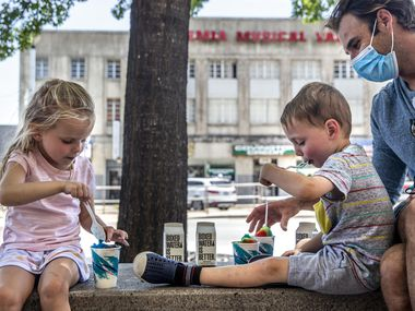 From left, siblings Victoria West, 4, and Preston, 3, enjoy rainbow snow cones from NOLA Snoballs with their father, Brian Bleeker along the Jefferson Boulevard business center in Oak Cliff in Dallas on Sunday, July 12, 2020.
