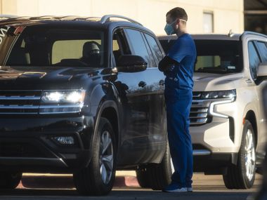 A medical professional, right, speaks with a driver of an SUV as he waits to receive a COVID-19 test outside of Frontline ER in Dallas, on Tuesday, Dec. 01, 2020.