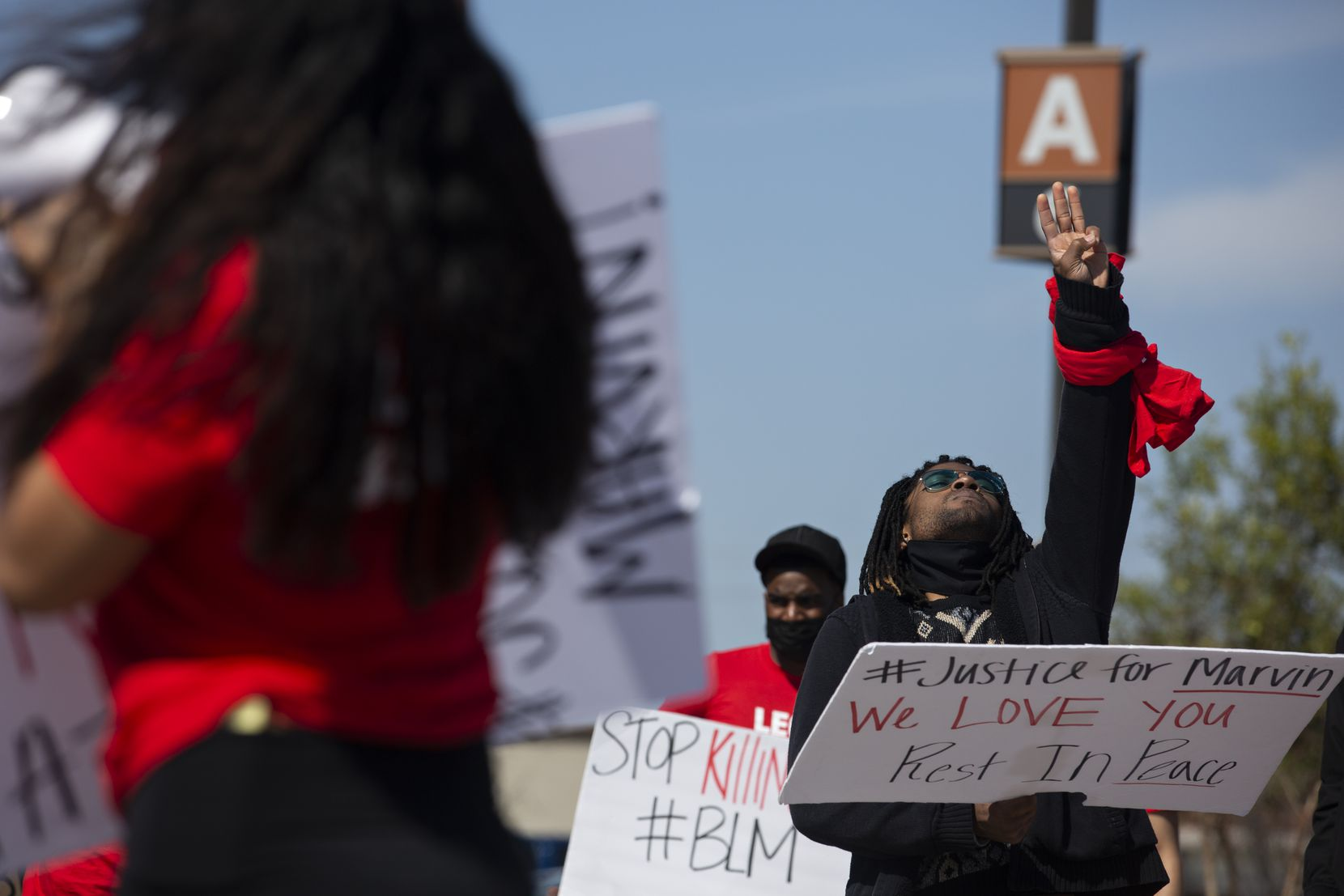 Quinten Scott holds up three fingers during a march through the Allen Outlets on Sunday, March 21, 2021 for his older brother Marvin Scott III, who died a week prior while in custody at the Collin County Jail on March 14, 2021. ÒIÕm just now to a point where I feel I can speakÓ, said Quinten after leading several chants and telling the crowd fond stories of his older brother. (Shelby Tauber/Special Contributor)