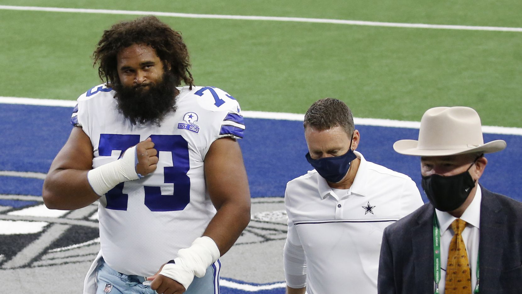 Dallas Cowboys center Joe Looney (73) signals towards his family in the stands as he exits the field with the Dallas Cowboys medical team in a game against the Cleveland Browns during the first half of play at AT&T Stadium in Arlington, Texas on Saturday, October 4, 2020.