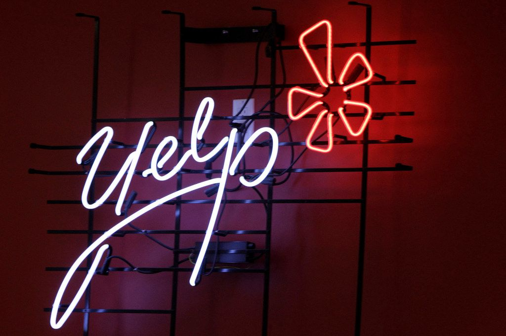 FILE - This Oct. 26, 2011, file photo shows the logo of the online reviews website Yelp in neon on a wall at the company's Manhattan offices in New York. A divided California Supreme Court has ruled that online review site Yelp.com cannot be ordered to remove posts against a San Francisco law firm that a judge determined were defamatory. The 4-3 ruling on Monday, July 2, 2018, came in a closely watched case that internet companies warned could be used to silence online speech. (AP Photo/Kathy Willens, File)