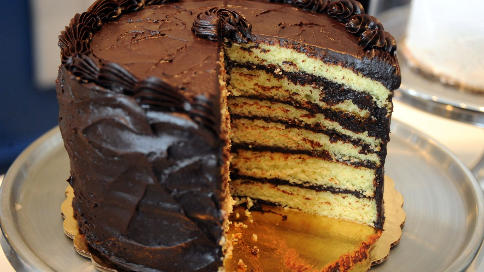 A slice of yellow cake with dark chocolate frosting from Cake Bar in Trinity Groves evokes happy childhood memories.