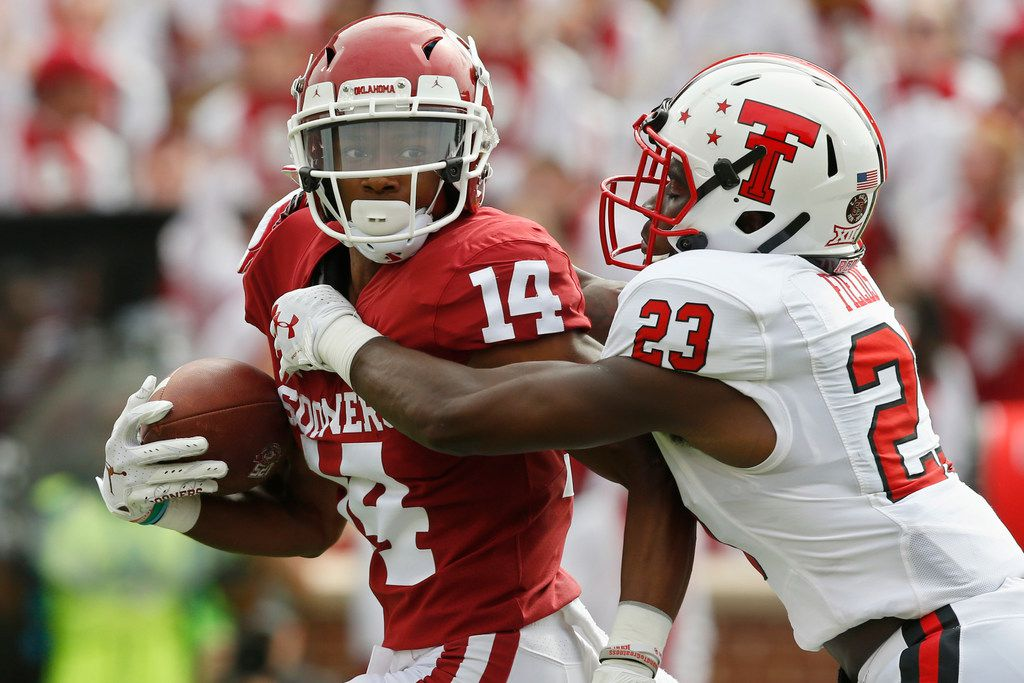 FILE - Texas Tech defensive back Damarcus Fields (23) tackles Oklahoma wide receiver Charleston Rambo (14) during the first quarter of a game in Norman, Okla., on Saturday, Sept. 28, 2019.