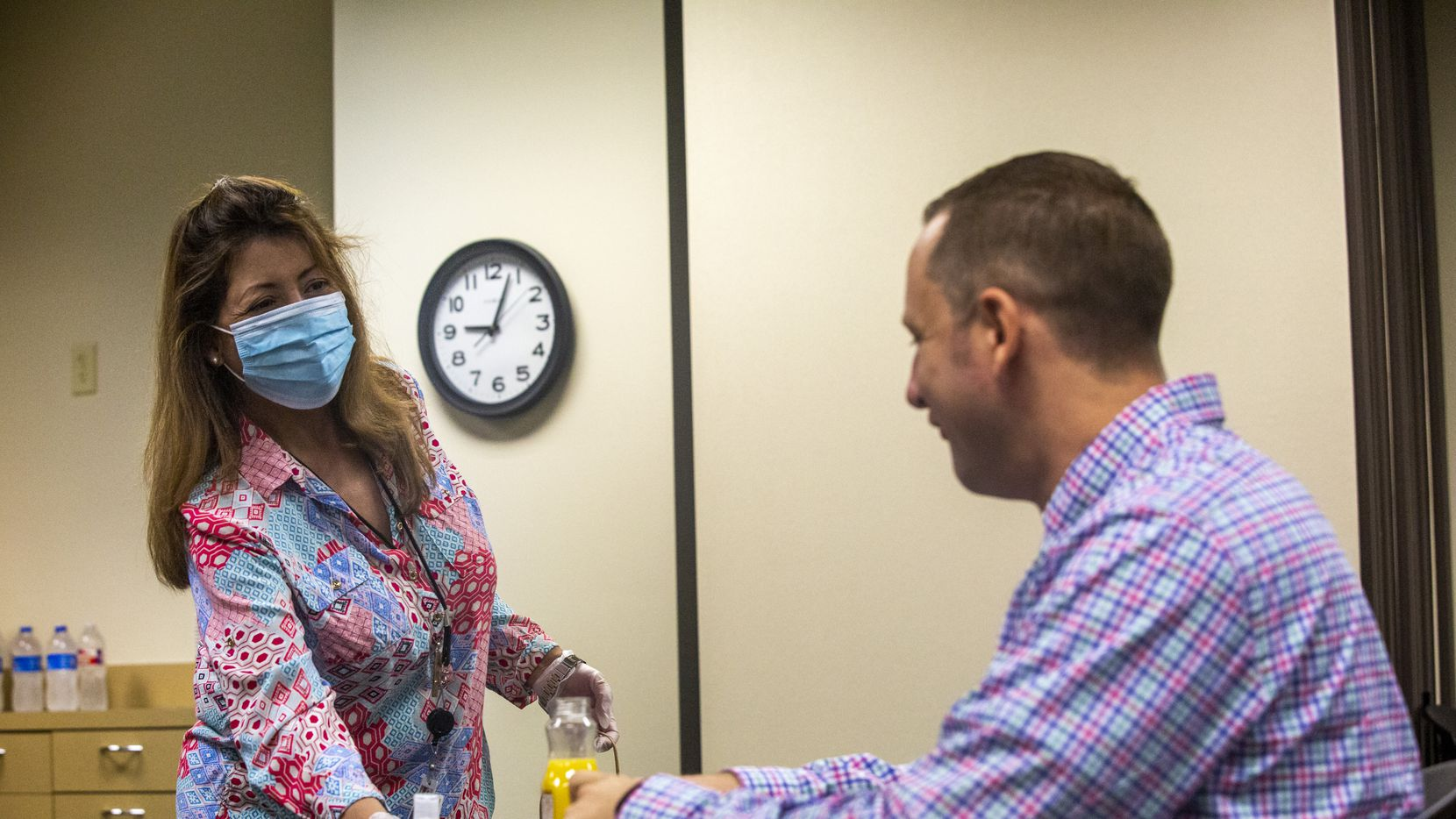Administrative Assistant Robbie Marquez (left) hands a hand sanitizer bottle to new hire and Quality Assurance Analyst Daniel Stirrat during a meet-and-greet breakfast with new company hires at the VPay Inc. office in Plano on Aug. 31, 2020. (Lynda M. González/The Dallas Morning News)
