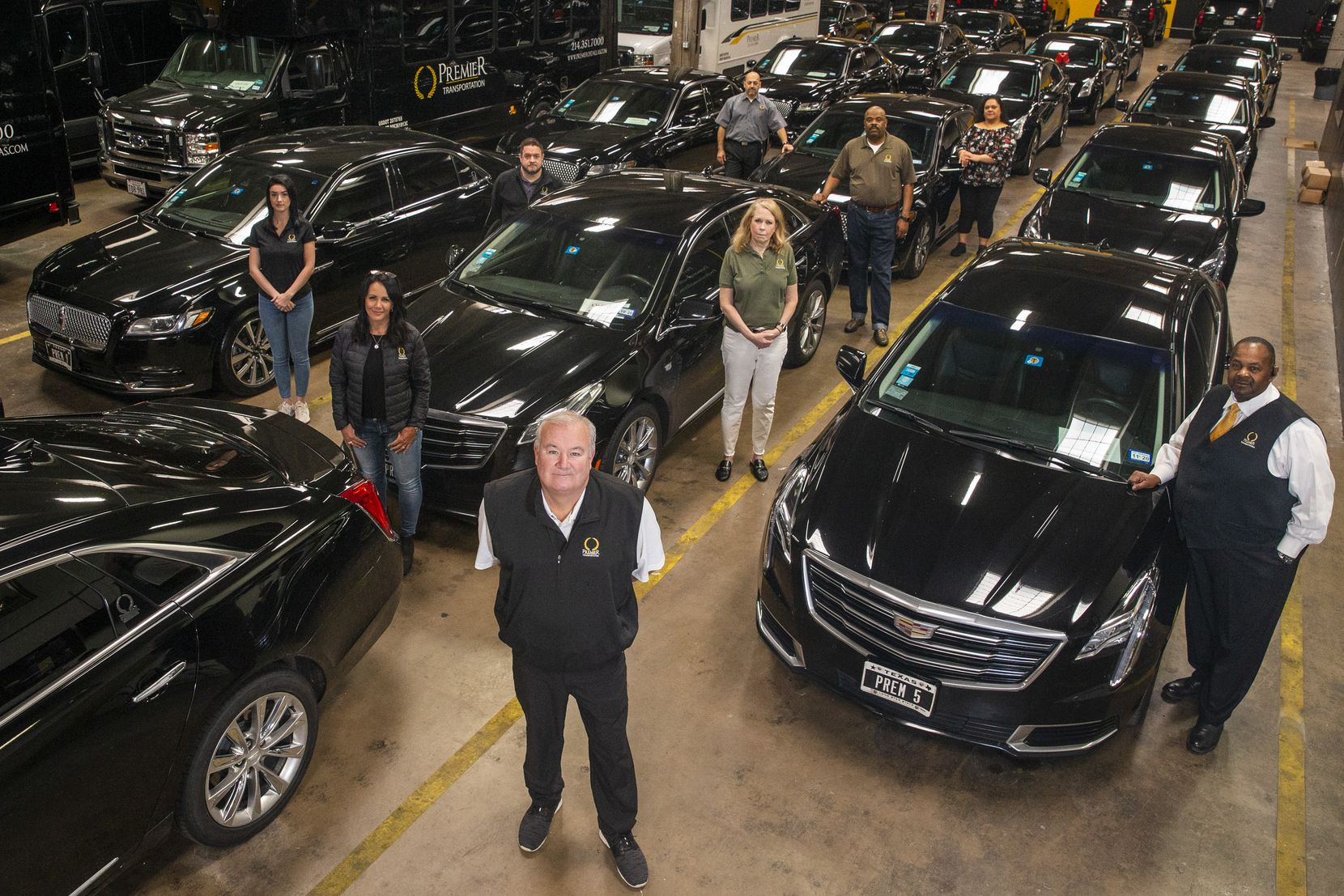 Premier Transportation owner Eric Devlin (center) and his employees pose at the company's headquarters in Dallas.