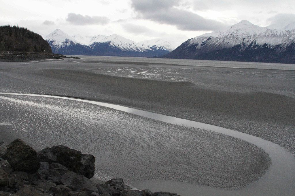 A ribbon of water cuts through the mud flats of Cook Inlet, just off the shore of Anchorage, Alaska. In 2017, a Hilcorp helicopter spotted bubbles at the surface and reported a leak from an underwater pipeline. The methane leak raised concerns among federal wildlife authorities about harm to endangered beluga whales.