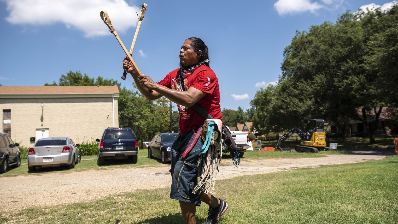 """Eli Hickman, 40, of Choctaw/Navajo people, plays a Native American stick ball game translated to """"Little Brother of War"""" during a community awareness event hosted by American Indian Heritage Day in Texas, Sept. 05, 2020 at the Dallas Indian Mission United Methodist Church. The event provided information about COVID-19, the 2020 Census and registered people to vote. Volunteers also handed out face coverings, free school supplies and """"Indian tacos."""""""
