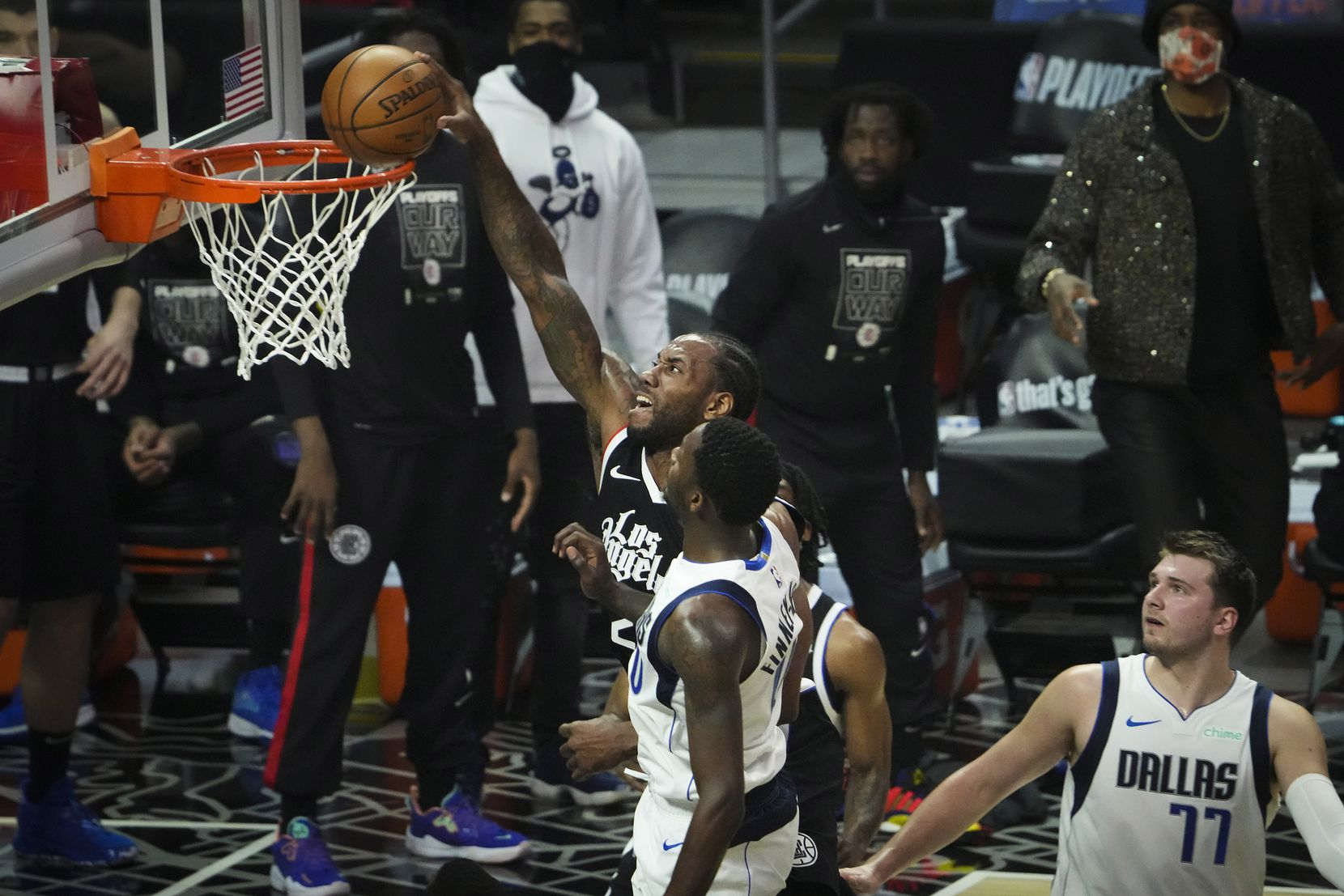 LA Clippers forward Kawhi Leonard (2) dunks the ball past Dallas Mavericks forward Dorian Finney-Smith (10) and guard Luka Doncic (77) during the first quarter of Game 7 of an NBA playoff series at the Staples Center on Sunday, June 6, 2021, in Los Angeles.