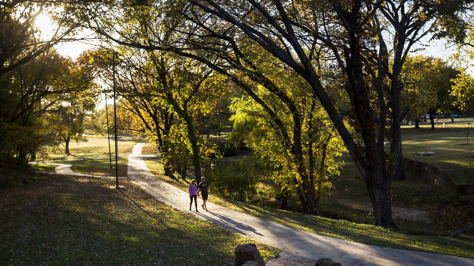 Walkers stroll along the paved trails and historic stonework established during the Works Progress Administration era at Reverchon Park. Staff photograph taken Oct. 20, 2020.