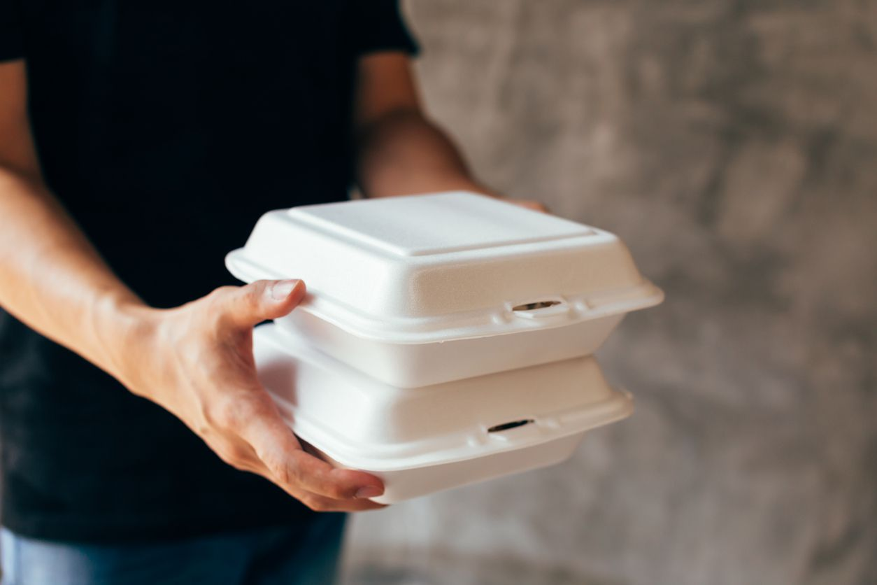 Una persona entrega comida en contenedores desechables.