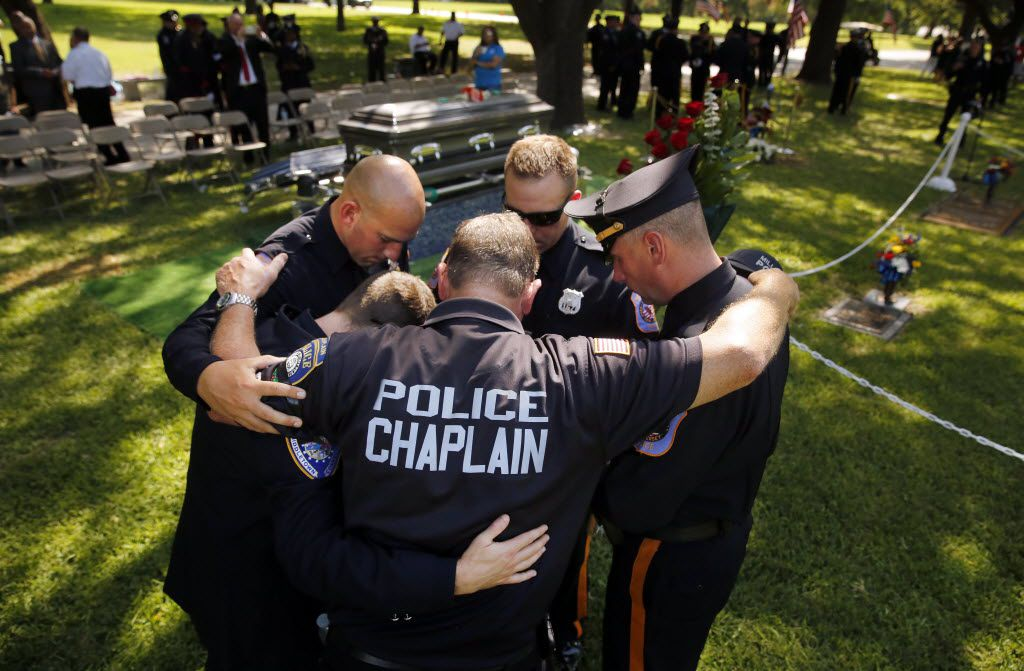 Millville (New Jersey) police chaplain Robert Ossler (center) prays with (from left) Middletown (Connecticut) police officer Ryan Jeffries, North Brunswick (New Jersey officers Joe Grasso, Ryan Uzunis, and Brian Hoiberg following the graveside service for slain Dallas police Sgt. Michael Smith at the Restland Funeral Home and Cemetery in Dallas, Thursday, July 14, 2016. Smith was gunned down in an ambush attack in downtown Dallas a week ago. Four Dallas police officers and one DART officer were killed. (Tom Fox/The Dallas Morning News)