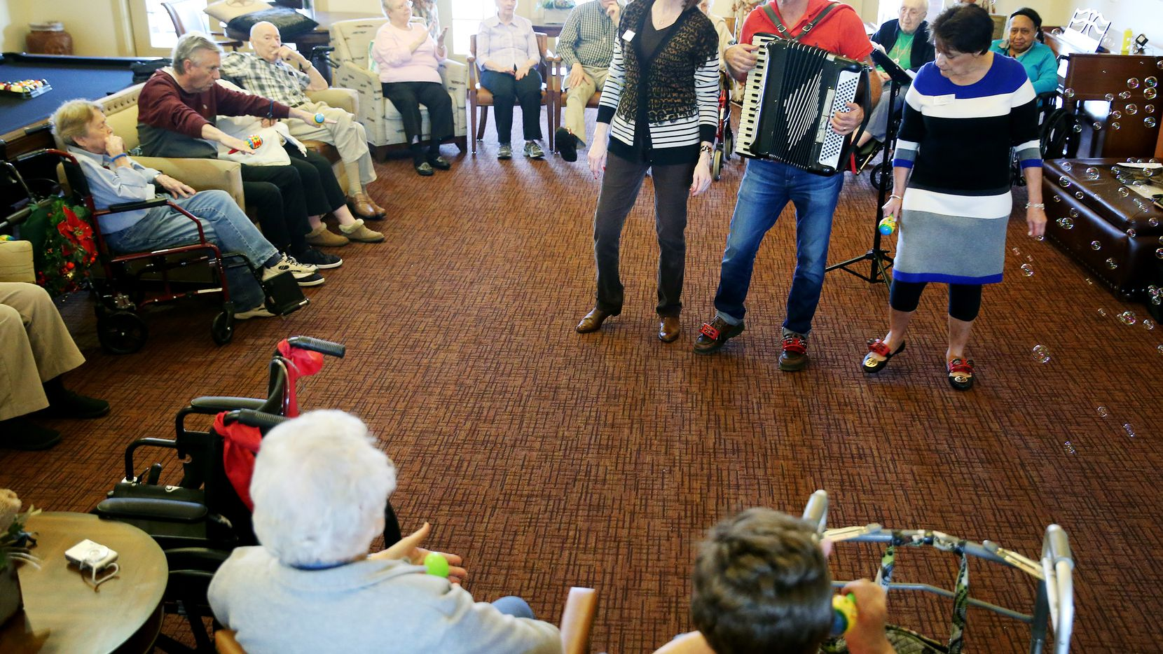 """Mike Frankel, known as """"Mike The Accordion Player,"""" played and sang with engagement directors Gale Janosek (left) and Diane Byers in 2016 at Vitality Texas Star Senior Living in Allen."""