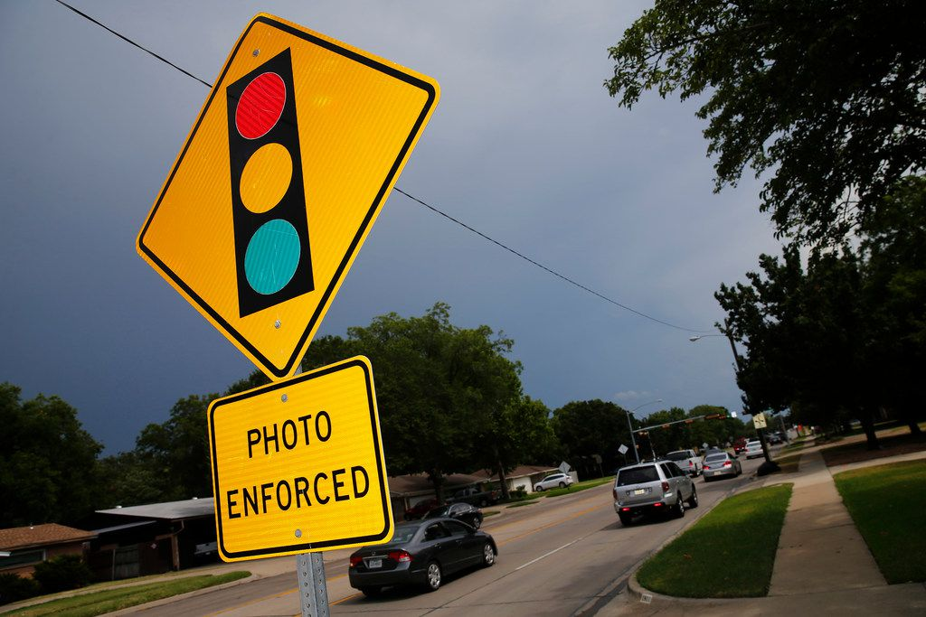 A sign warns drivers of Irving's use of red-light cameras at O'Connor Road and Lane Street on July 6, 2018. On June 1, Gov. Greg Abbott signed a law outlawing traffic light cameras like these.