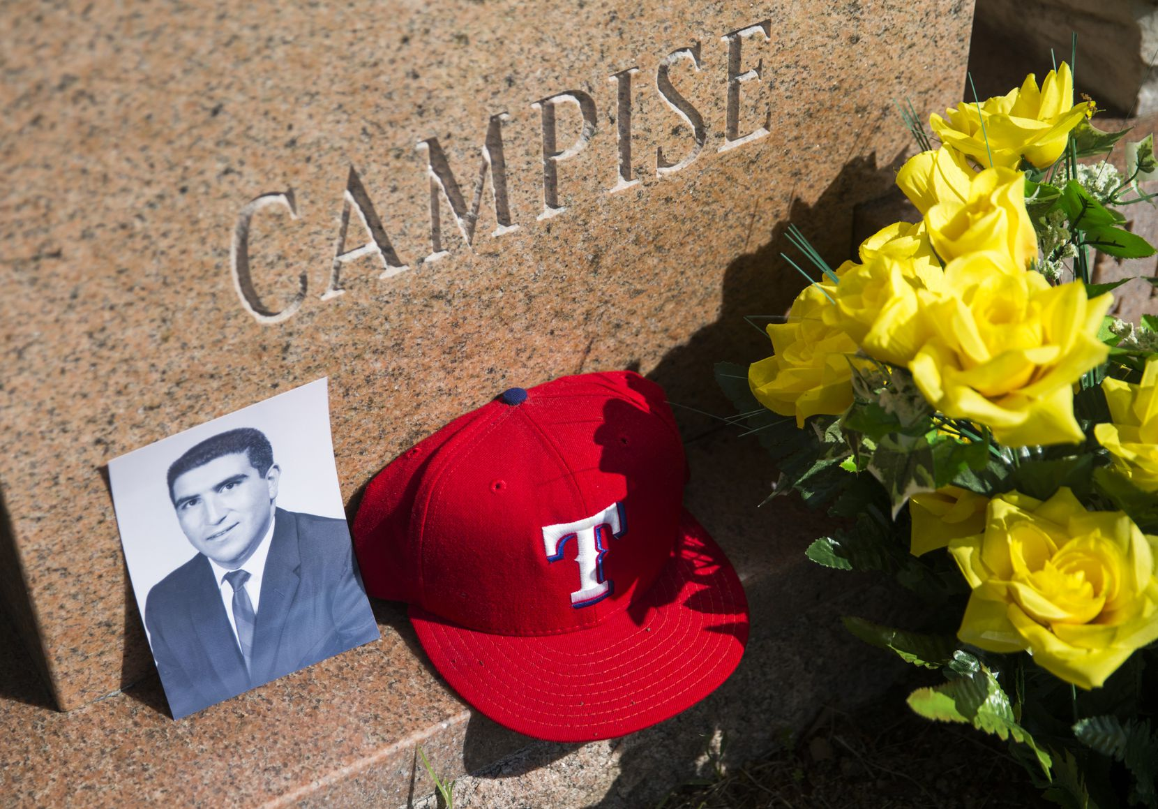 An old portrait of Frank Campise and one of his Texas Rangers hats were placed at his grave for a photo shoot at Calvary Hill Cemetery in Dallas. He died at age 80 on March 22.