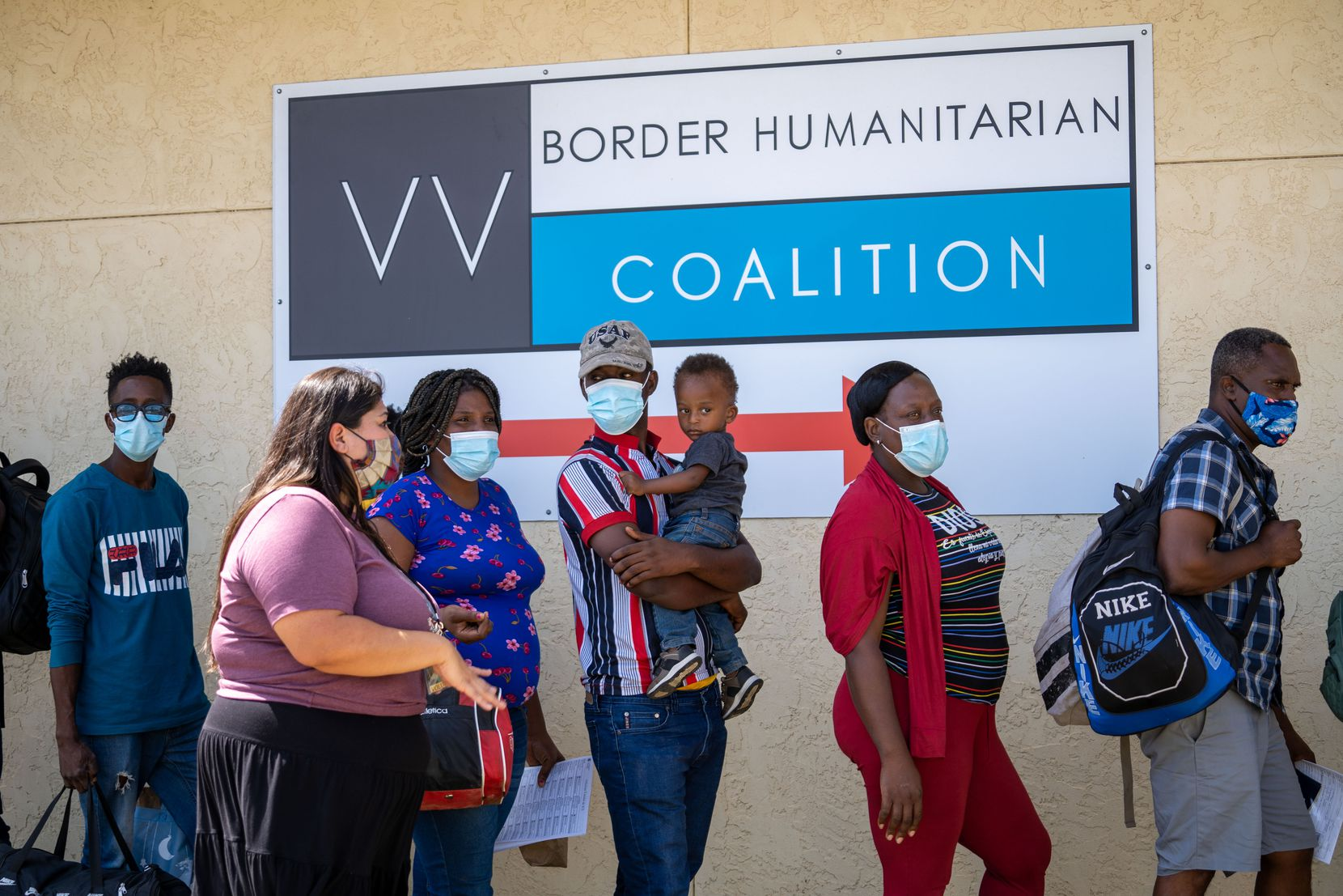 Migrants are greeted Lupita De La Paz at the Del Rio day shelter run by the Val Verde Border Humanitarian Center. Many planned to take a bus to Houston and final destinations. (Ro John Alviola /Special Contributor)
